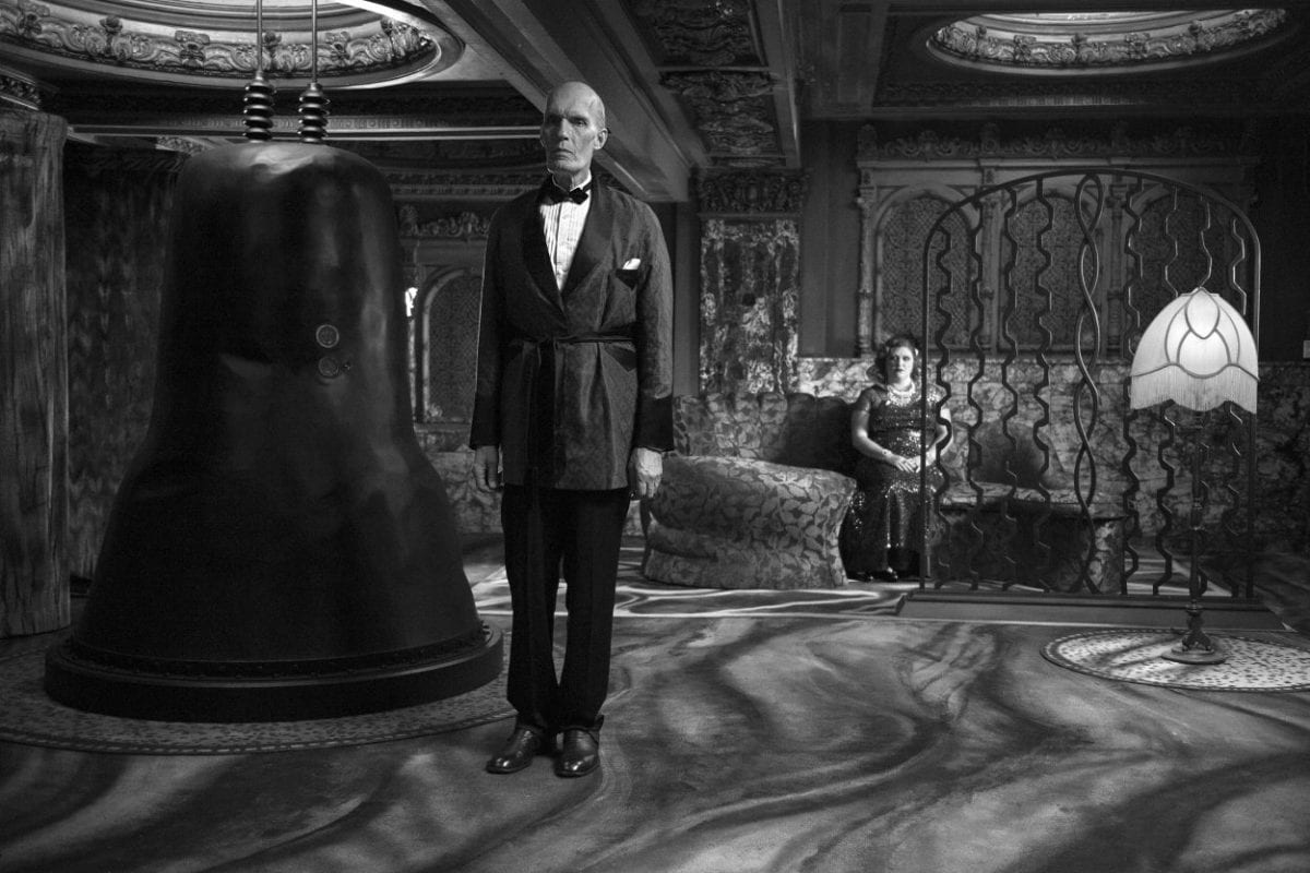 The Giant stands in the White Lodge with Señorita Dido sitting behind him