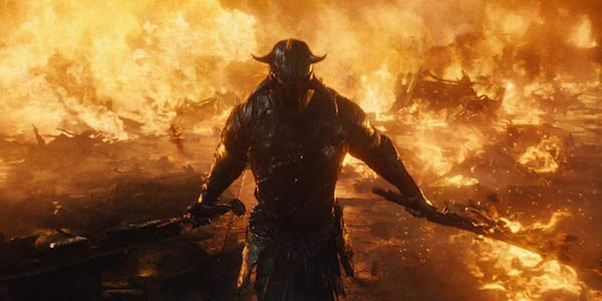 Ares in full armour, weilding two swords walking through a wall of fire.