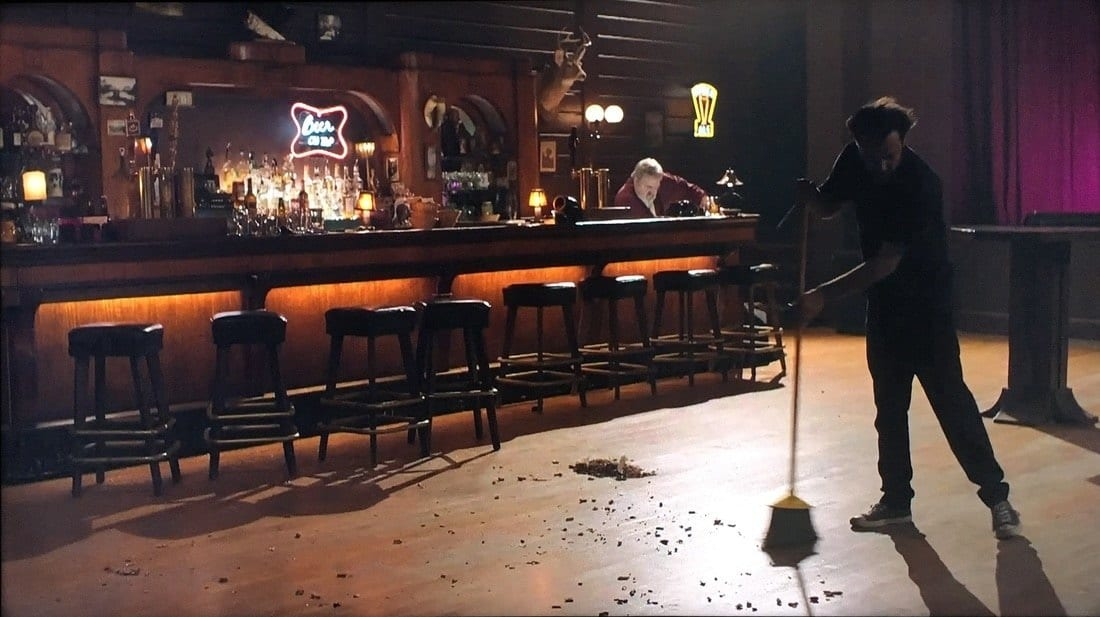 A wide shot of an empty bar with one man sweeping with a broom. Bartender is at the back cleaning the counter.