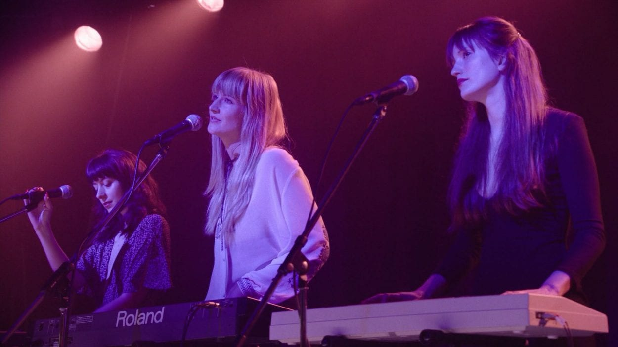 On a dutch angle, the three women sing into microphones. The woman closest to us is behind a keyboard.