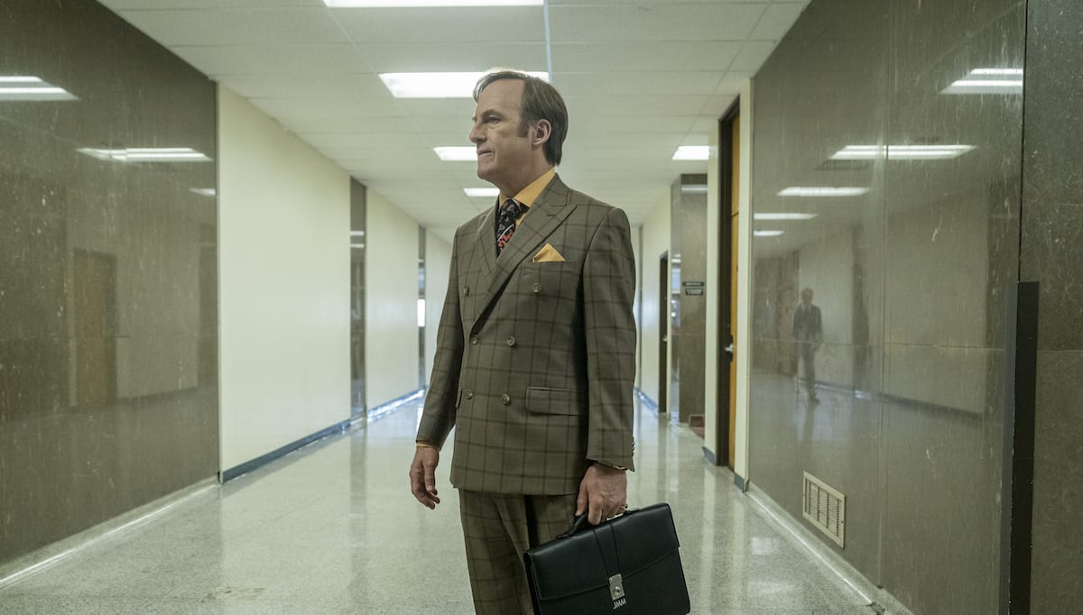 Jimmy stands in the courthouse hallway holding a briefcase and dressed in Saul Goodman attire