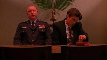 Bobby and the Major sit next to each other in the Birggs house before Laura's funeral