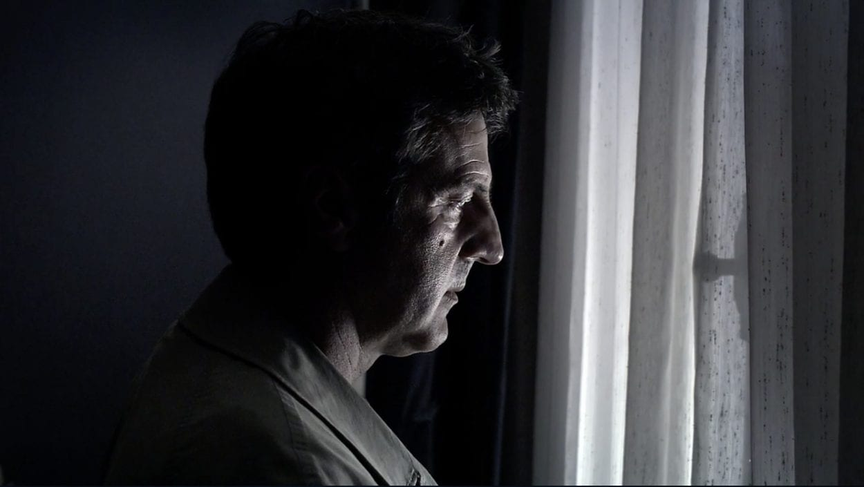 Georges (Daniel Auteuil) looks out onto the street to where his family is being watched