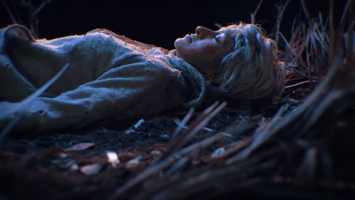 "A woman lies on the forest floor next to a tree in the video for ""Sat by a Tree"""
