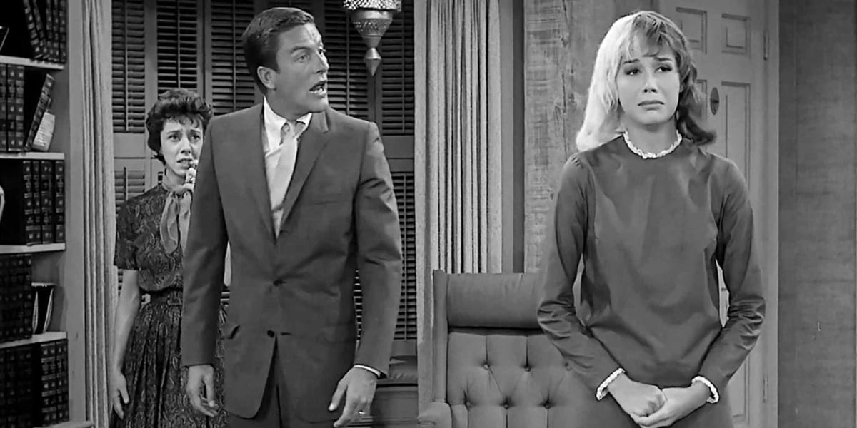 Mary Tyler Moore with half blonde half brunette hair with her hands clasped, Dick Van Dyke standing behind her staring at her in shock, Ann Guilbert standing behind Van Dyke with a worried look on her face