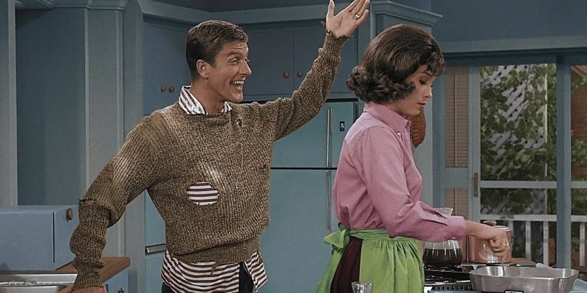 Dick Van Dyke smiling with one arm down and one arm up, Mary Tyler Moore with her back to him cooking eggs, picture is colorized
