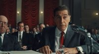 Jimmy Hoffa sits at a desk next to a lawyer with a microphone in front of his face