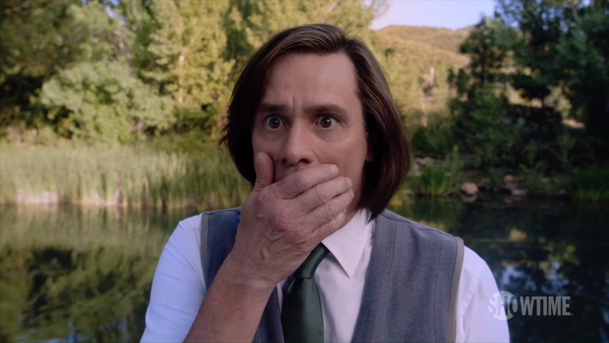 Jim Carrey stands in shock with his hand over his mouth