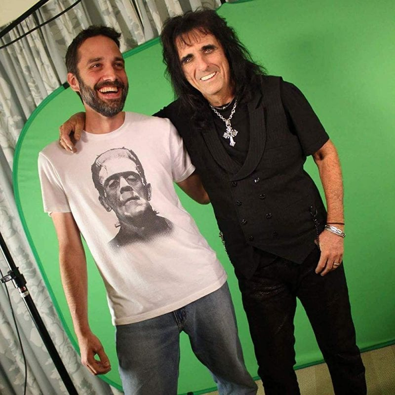 Justin Beahm wears a T-shirt with Frankenstein's monster on it and stands next to Alice Cooper, wearing all black and a cross necklace, in front of a green screen on a production set.