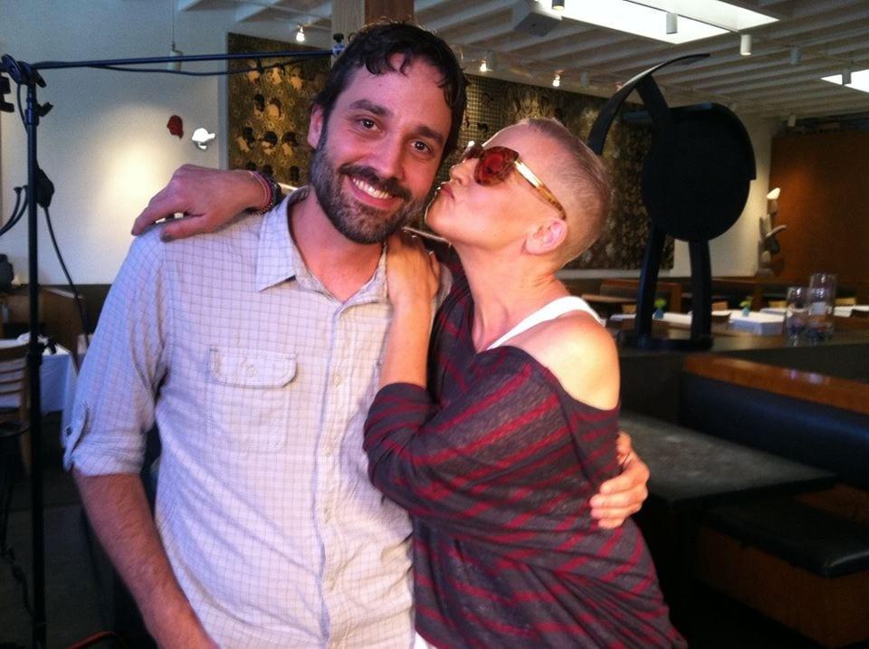 Lori Petty kisses Justin Beahm on a production set.