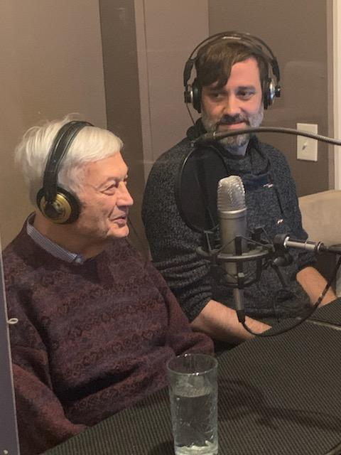 Two men talk to each other on a production set on microphones while wearing headphones, a glass of water in front of one of them.