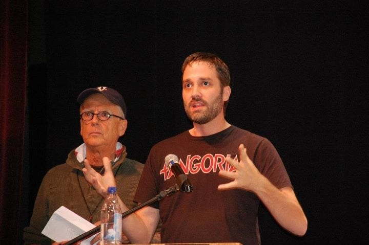 Justin Beahm wears a Fangoria T-shirt and talks on a microphone while Victor Miller stands next to him.