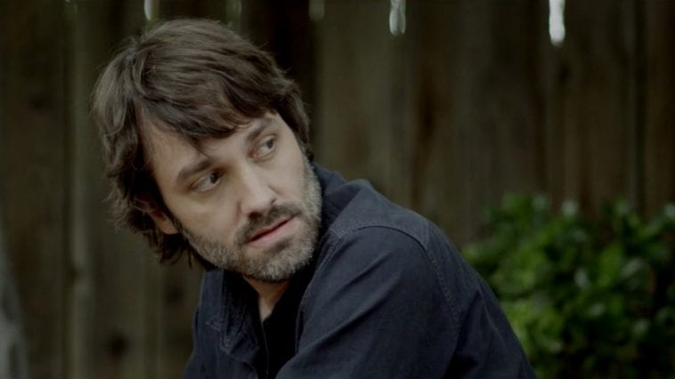 A man in a casual blue shirt and a bit of stubble sits outside and looks to his side reflexively.