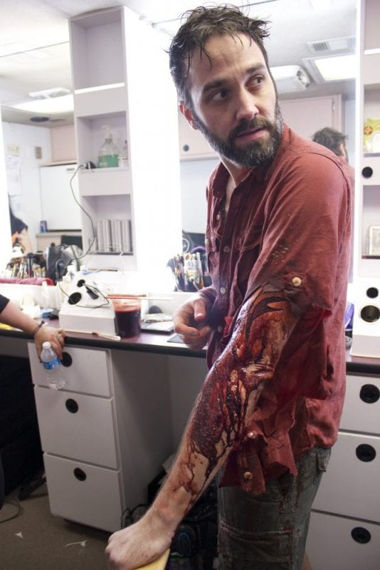 A man is in a special makeup effects studio, with wet hair and a fake wound and blood on his arm.