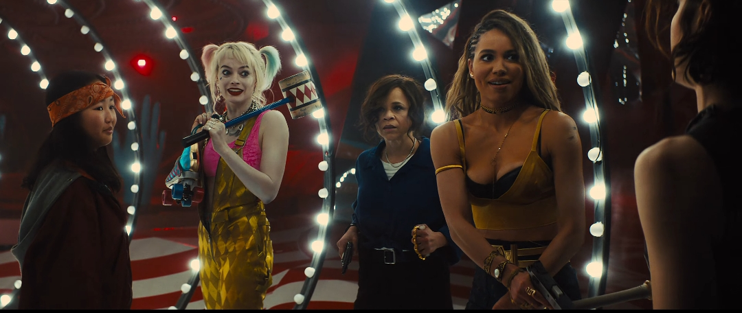 Harley Quinn and the others in a hall with lights running up the walls