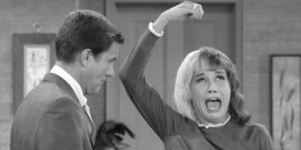 Mary Tyler Moore with an upset look on her face, her arm over her head with her fingers indicating she's holding something, her mouth open, Rob watching her, the image in black and white