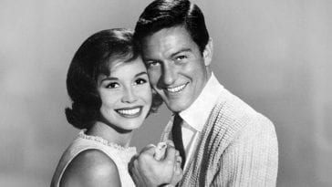 Mary Tyler Moore and Dick Van Dyke in black and white with their heads touching facing the camera with smiles on their faces