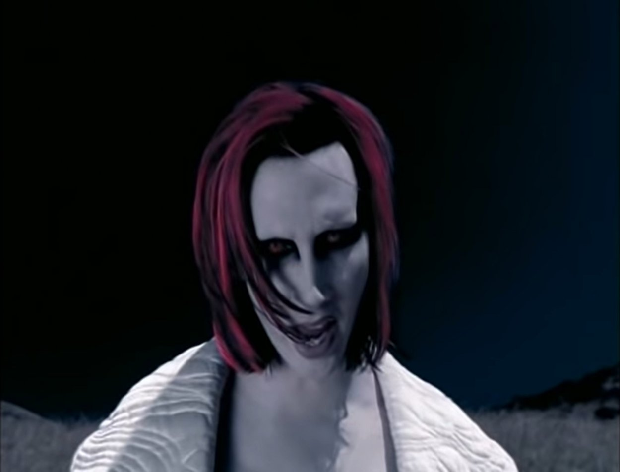 """Marilyn Manson as an alien standing against the night sky in """"The Dope Show"""" music video"""