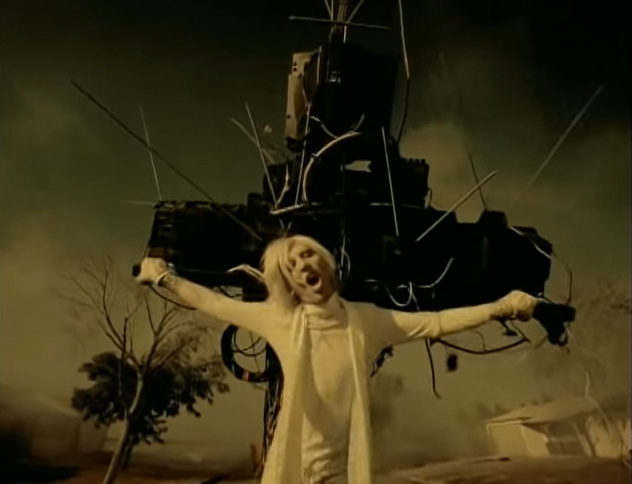 """Marilyn Manson hanging from a crucifix made of TVs in the """"I Don't Like the Drugs (But the Drugs Like Me)"""" music video"""