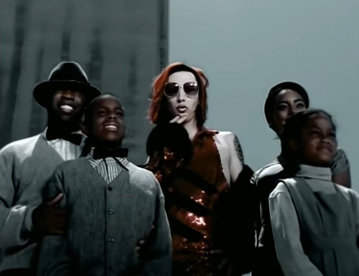 """Marilyn Manson as an alien rock star posing for the camera, surrounded by people wearing grey clothes in """"The Dope Show"""" music video"""