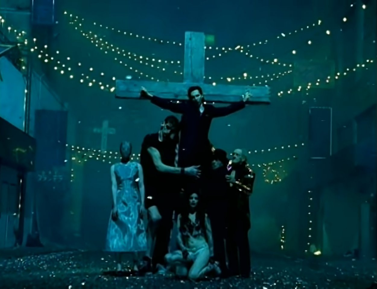 """Marilyn Manson hanging from a crucifix surrounded by an odd assortment of people in the """"Coma White"""" music video"""