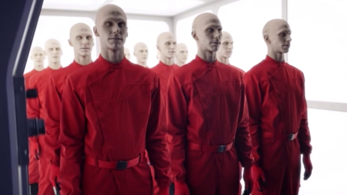 Picard S1E2 - A group of sythetics in red jumpsuits stand in formation in a small storage room