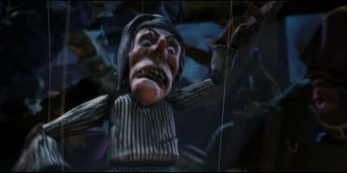 Scrooge puppet one arm down and one arm crooked facing upwards with a dark background in Polar Express