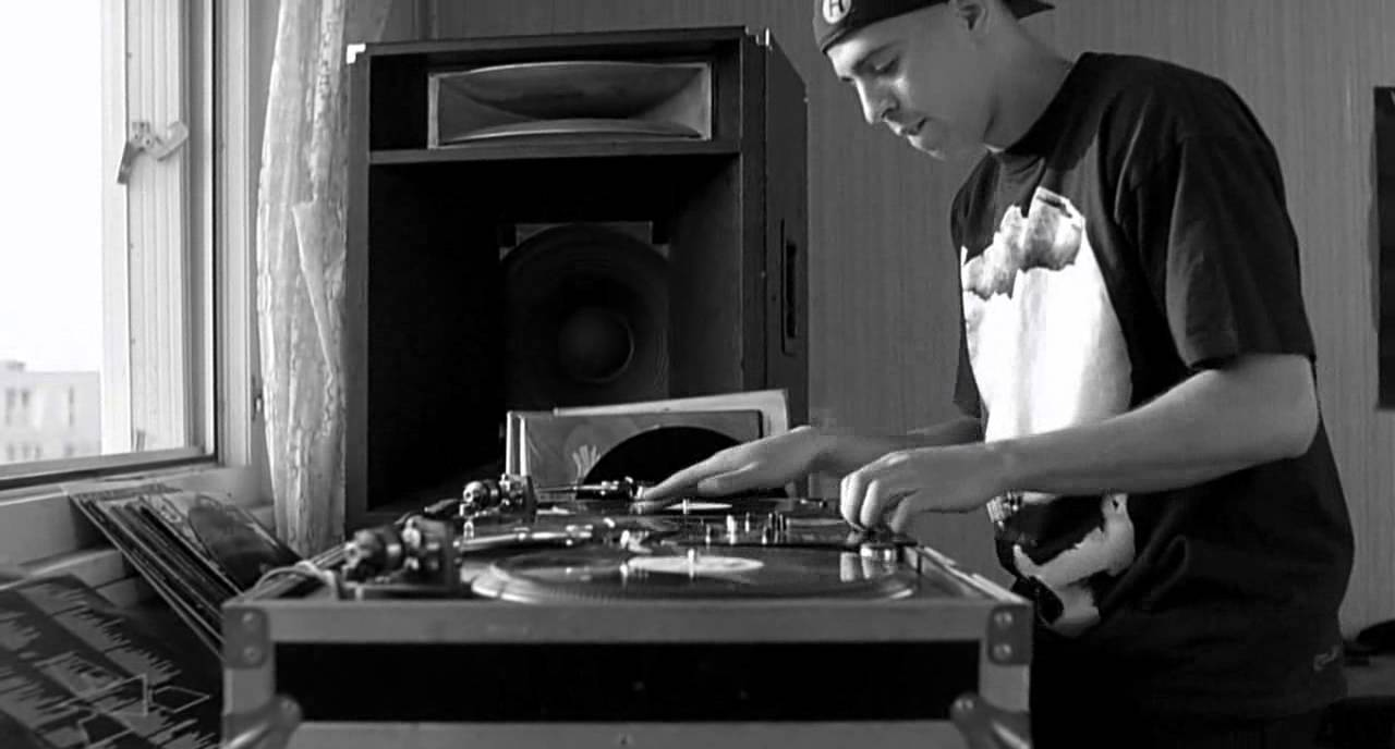 A DJ scratches records on decks set up in his bedroom
