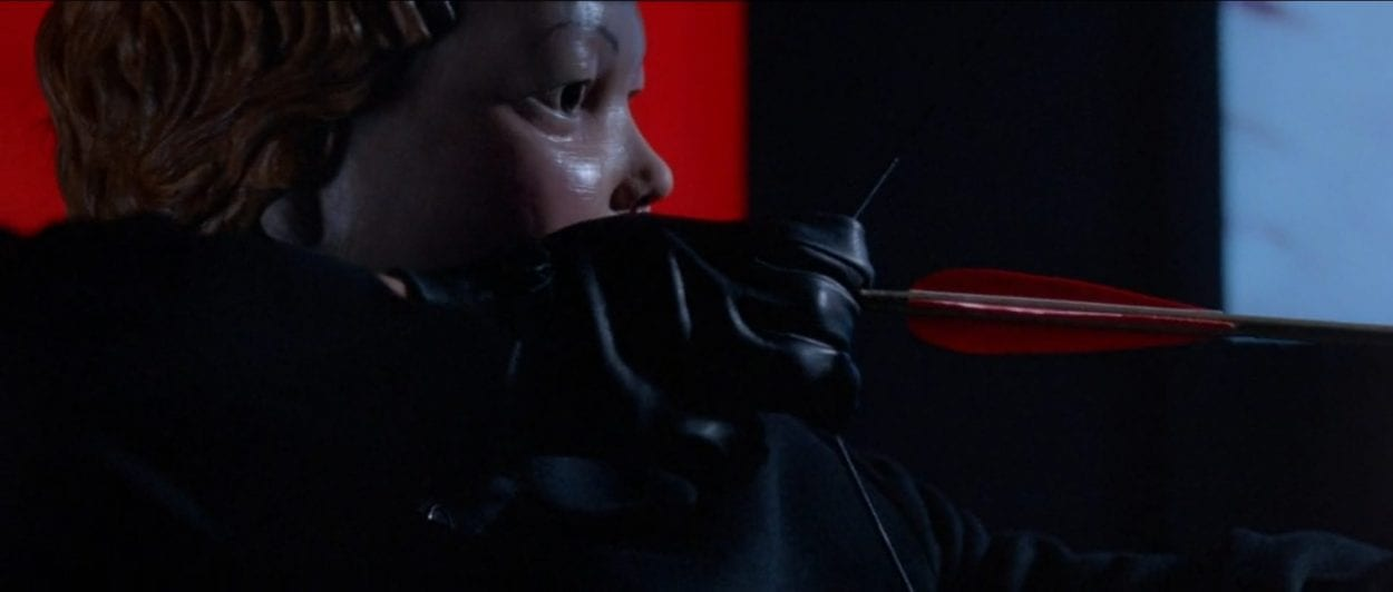 The cherub masked killer readying an arrow.