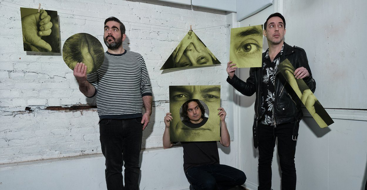 Dan Boeckner, Spencer Krug and Arlen Thompson from Wolf Parade hold photos while standing in a white room