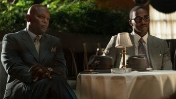 Samuel L Jackson and Anthony Mackie sit at a table in The Banker