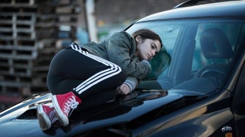 Clara lies on the bonnet of a car bored