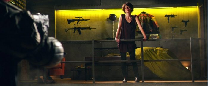 Ma-Ma stands on a balcony surrounded by her personal collection of firearms