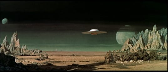 Flying saucer drifts over an alien desert