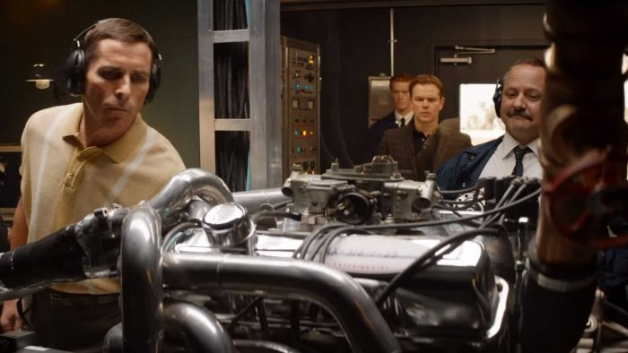Christian Bale, wearing headphones, Matt Damon, and a few others men look at a car engine