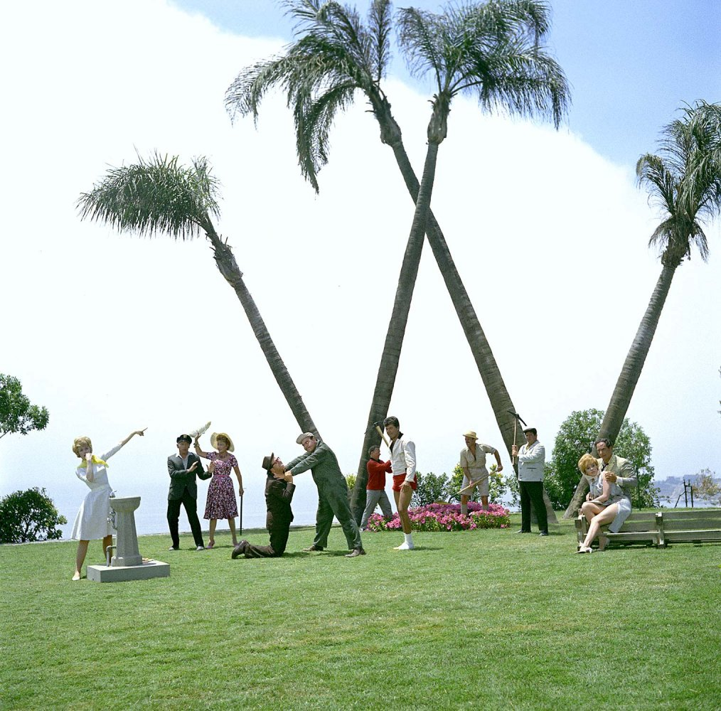 Publicity photo of the cast in character, posed in front of 4 palm trees that form a big W