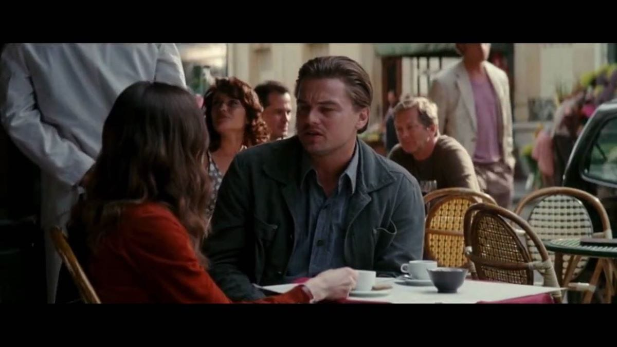Leonardo DiCaprio and Ellen Page talking at a table outside a cafe in Inception