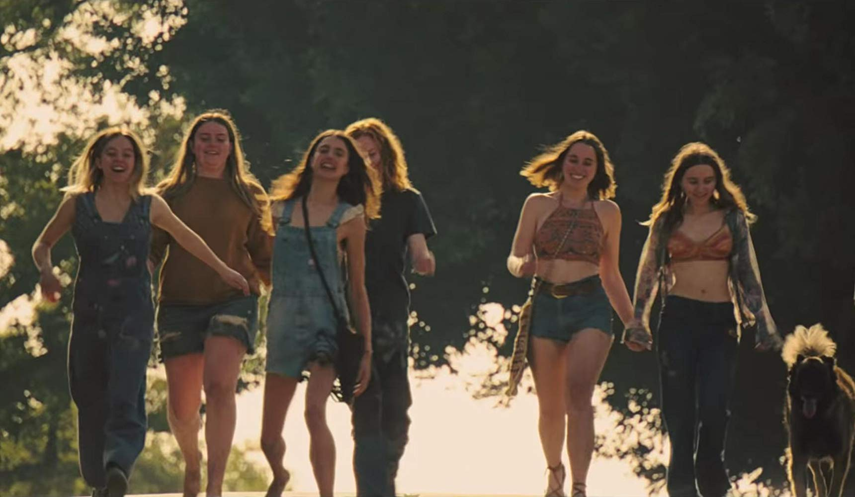 the girls of the manson family walk laughing and smiling together