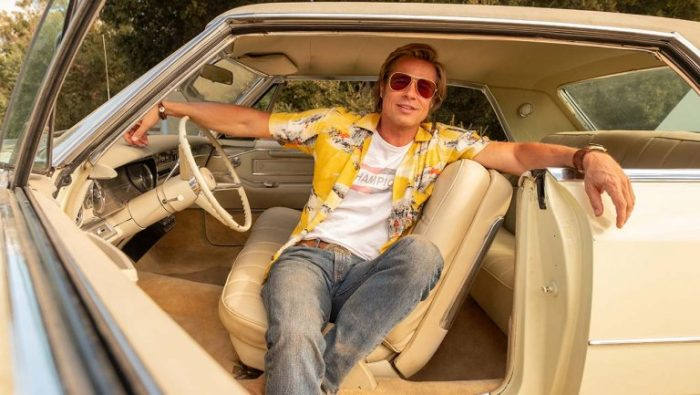 Brad Pitt sits in his car with a yellow Hawaiian shirt