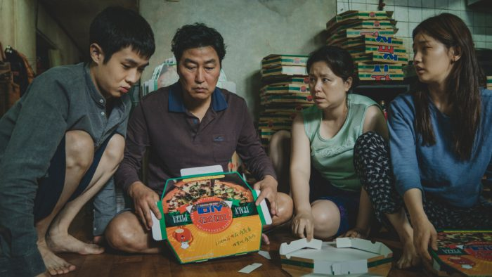 A South Korean family unfolds a pizza box in their living room