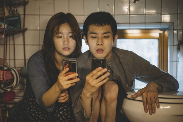 A man and woman sit next to a toilet looking at their phones