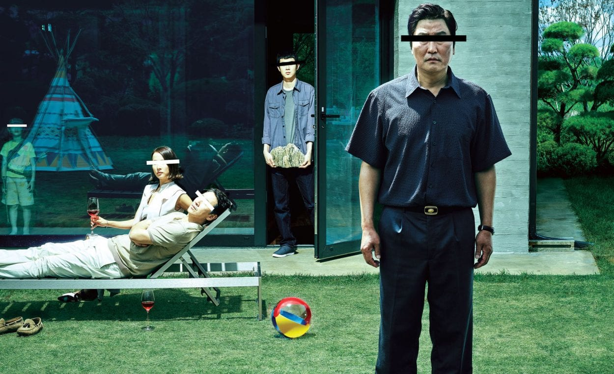 A promotional shot for Parasite, with the four main characters standing or sitting right outside of a house, all with censor bars over their eyes