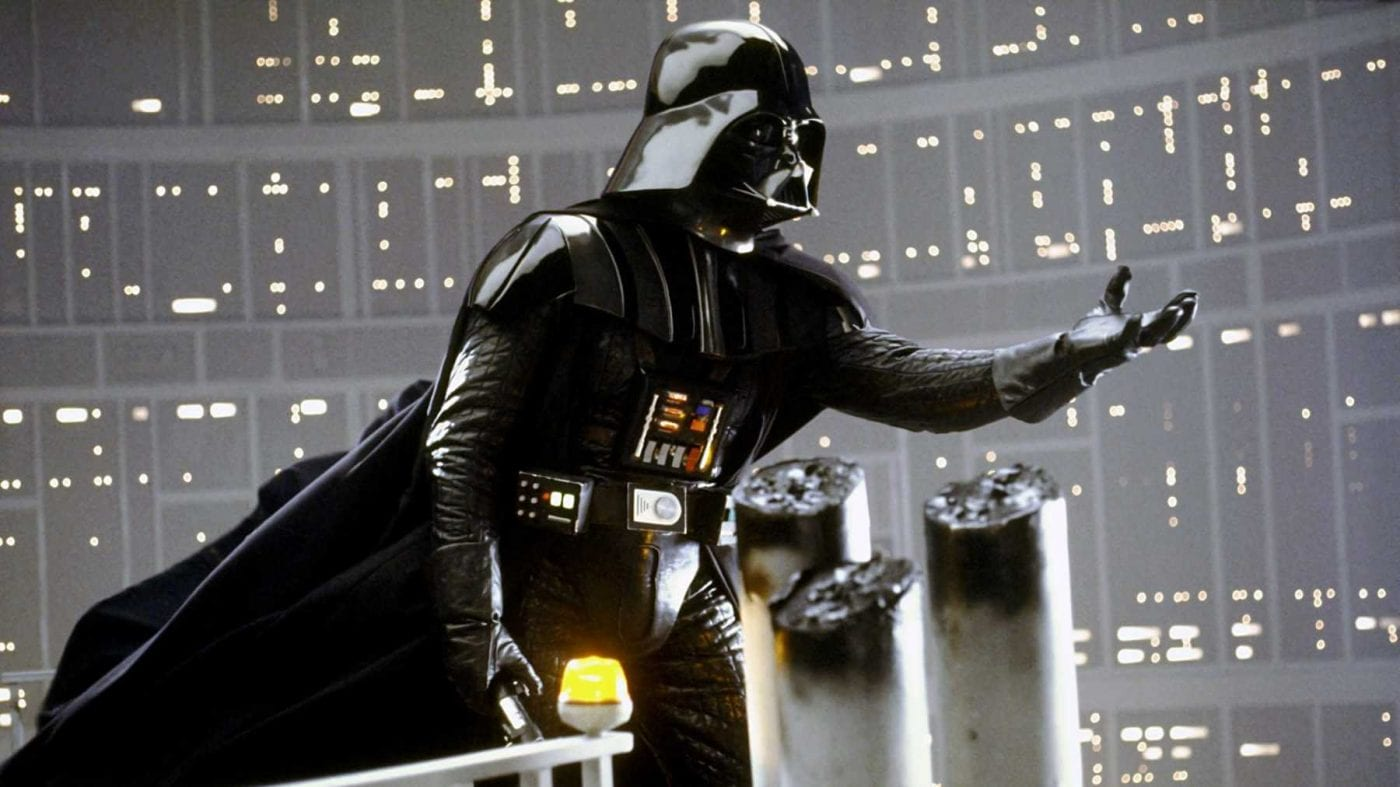 Darth Vader stading at the edge of a platform, holding out his hand