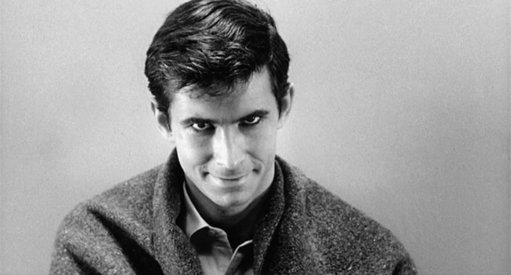 Norman Bates looking at the viewer with a devilish smile
