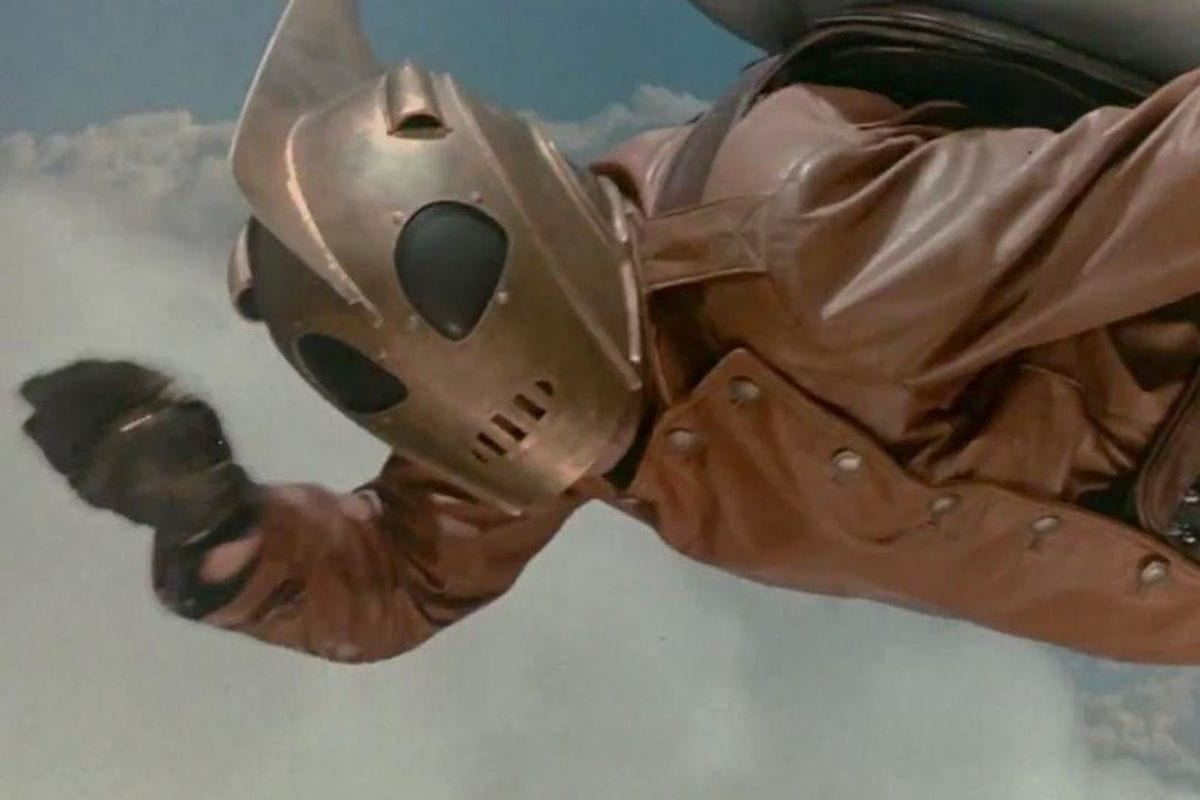 The Rocketeer flying in his iconic helmet and rocket pack.
