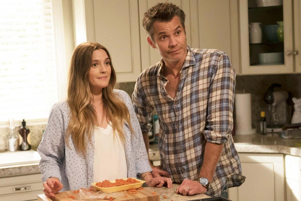 Sheila (Drew Barrymore) and Joel (Timothy Olyphant) stand next to each other in the kitchen in front of a package of raw meat.