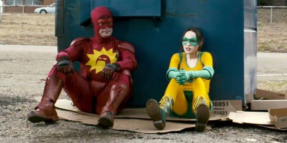 A man and a young woman are sitting dressed as superheros sat in front of a bin
