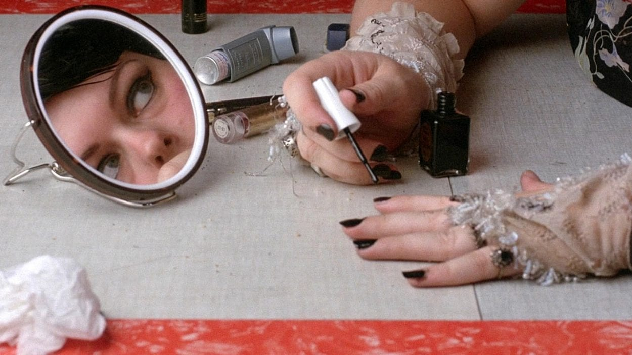 a reflection of a womans face in a mirror as she paints her nails, in Sweetie
