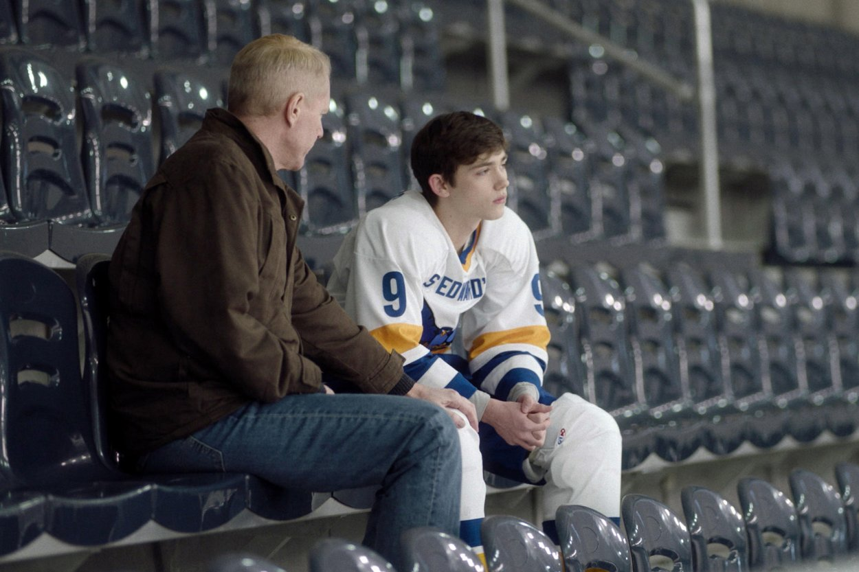 Stan talks to Henry in the stands of the hockey rink. Henry, wearing his hocket uniform, is clearly upset