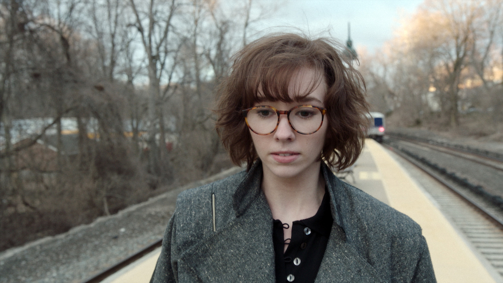 Paige wearing her disguise with glasses walks down the train platform